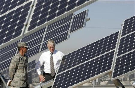 Lt. Col. Patrick Fogarty (L), Nellis Air Force Base engineer, and Alan Shaffer, principal deputy director for defense research and engineering plans and programs, look over solar photovoltaic panels during a tour of the solar array at the base in Las Vegas, Nevada in this picture taken August 1, 2008. REUTERS/Steve Marcus (UNITED STATES)