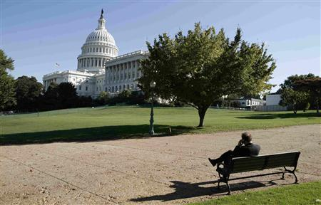 A man sits on a bench in front on the House of Representatives wing of the Capitol building in Washington October 2, 2008. The House is expected to vote Friday on the $700 billion financial rescue plan which was passed by the Senate last night. REUTERS/Kevin Lamarque