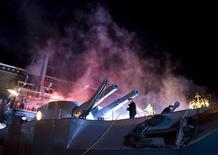 <p>Sailors perform a mock sea battle on a fake war vessel in front of a Moscow cinema to promote Russia's latest blockbuster, October 6, 2008. REUTERS/Thomas Peter</p>