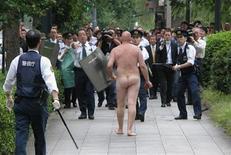 <p>Un hombre desnudo se enfrenta a la policía en Tokio, 7 oct 2008. Un hombre calvo y desnudo, que aseguró ser español, se bañó el martes en el foso del Palacio Imperial de Japón, subió los muros del edificio mientras que arrojó piedras y agua contra la policía antes de ser detenido. REUTERS/Kyodo</p>