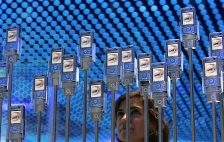 A woman poses next to cell phones at the 'Internationale Funkausstellung' (IFA) 2006 consumer electronics fair in Berlin, September 1, 2006. REUTERS/Tobias Schwarz