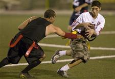 <p>Amirhossein Sahiholnasab (R) tries to evade a tackle during the Tehran Titans flag football game at Tehran's Shahid Keshvari stadium October 6, 2008. REUTERS/Caren Firouz</p>
