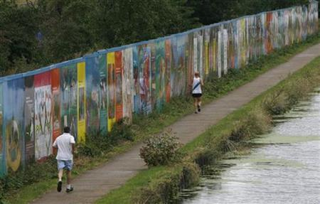 Joggers run past a barrier which shields London's Olympic Park building site from view next to a canal August 24, 2008. REUTERS/Andrew Winning