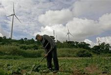 <p>A farmer works near wind turbines in the Sierra del Rey mountain range, about 100km (62 milles) from Lisbon June 2, 2008. REUTERS/Nacho Doce</p>