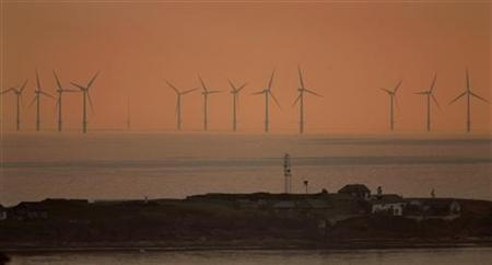 The sun sets behind the North Hoyle offshore wind farm in the Irish sea off the coast of northwest England, July 22, 2006. REUTERS/Phil Noble