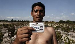<p>Inmate Vitor Grilo shows his prisoner card during the grape harvest at the Pinheiro da Cruz prison vineyard in Grandola, southern Portugal, October 1, 2008. REUTERS/Nacho Doce</p>