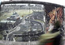 <p>Un turista camina al lo largo de la galería de arte 'East Side Gallery' en Berlín, 15 oct 2008. Los murales sobrevivientes en la sección más larga del muro de Berlín, que constituyen la galería de arte al aire libre más extendida del mundo, serán sometidos a una restauración de emergencia para salvarlos de su deterioro, dijo uno de los organizadores el jueves. REUTERS/Tobias Schwarz (ALEMANIA)</p>