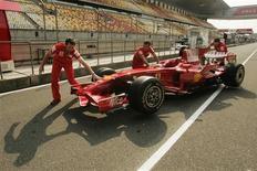 <p>Mecânicos da Ferrari empurram carro da equipe no circuito de Xangai, nesta quinta-feira, na preparação para o GP da China do fim de semana. REUTERS/Aly Song</p>