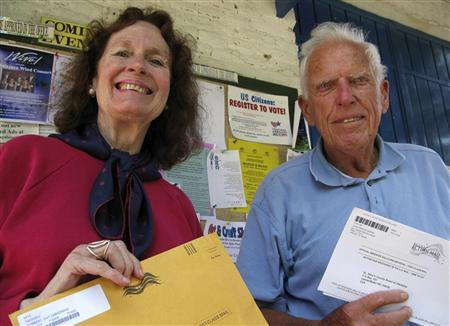 Democrat voters Day Dobbert (L) and John Wester hold their completed U.S. election ballots ready for posting in the town of Ajijic in Mexico's state of Jalisco October 13, 2008. REUTERS/Catherine Bremer