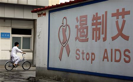 A member of the medical staff at the Beijing You An Hospital rides a bicycle past a sign regarding AIDS October 17, 2008. REUTERS/David Gray