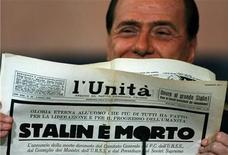 <p>Immagine d'archivio del presidente del Consiglio Silvio Berlusconi con una copia d'archivio dell'Unità del 1953 che annunciava la morte del ledaer sovietico Joseph Stalin. REUTERS/Chris Helgren</p>