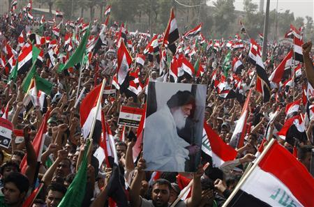 Demonstrators wave Iraqi national flags during a protest march in Baghdad's Sadr City October 18, 2008. Thousands of followers of anti-American cleric Moqtada al-Sadr took to the streets on Saturday in a demonstration against a pact that would allow U.S. forces to stay in Iraq for three more years. REUTERS/Kareem Raheem
