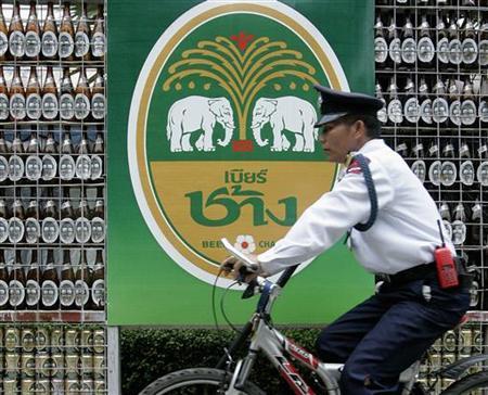 A security guard rides his bicycle past a beer advertisement at a market in Bangkok October 17, 2006. REUTERS/Sukree Sukplang
