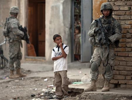 An Iraqi boy looks as U.S soldiers patrol Baquba, in Diyala province some 65 km (40 miles) northeast of Baghdad October 19, 2008. REUTERS/Goran Tomasevic