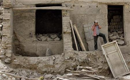 A boy speaks on a mobile phone as he stands in front of a ruined house in Kabul August 6, 2008. REUTERS/Adnan Abidi