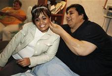 <p>Manuel Uribe looks at the earrings of his fiancee Claudia Solis at his home in the suburb of San Nicolas de los Garza, Monterrey October 24, 2008. Uribe, who once weighed 1,235 pounds (560 kilograms), will marry Solis on Sunday after losing nearly half his original body weight. REUTERS/Tomas Bravo</p>