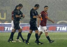 <p>Il capitano della Roma, Francesco Totti, e l'arbitro Paolo Tagliavento abbandonano il campo dopo che la partita di serie A Roma-Sampdoria è stata sospesa per il nubifragio che si è abbattutto sulla città. REUTERS/Giampiero Sposito</p>