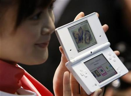 A promoter for Nintendo Co Ltd poses with the new DS handheld game console after a news conference in Tokyo October 2, 2008. REUTERS/Kim Kyung-Hoon