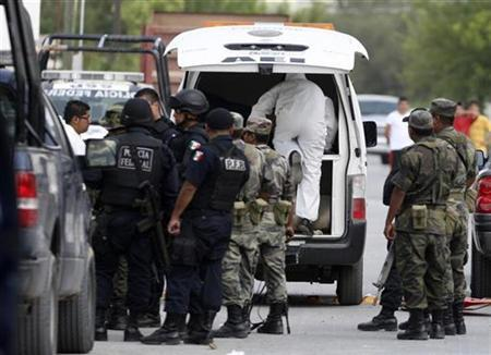 Federal policemen and soldiers gather outside a house after a shootout in the Mexican municipality of China, some 120 km (74.56 miles) northeast of Monterrey, in this file photo from September 28, 2008. REUTERS/Tomas Bravo