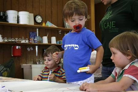 Kreyndl Neuberg, age two and a half and wearing a T-shirt that reads ''meydele,'' or ''young girl'' in Yiddish, stands between Sholem Burshtin (L) and Mekhayele Burshtin (R) as the three work on an art project at Yiddish Week in Copake, New York, August 24, 2008. REUTERS/Helen Chernikoff