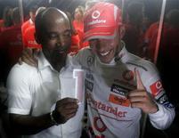 <p>O piloto de Fórmula 1 da McLaren, Lewis Hamilton (dir) comemora com o pai, Anthony Hamilton, vitória no GP do Brasil em 2 de novembro. O pai do novo campeão de Fórmula 1 disse que insultos racistas e abusos têm lhe provocado dúvidas sobre se seu filho deve continuar competindo no esporte. REUTERS/Bruno Domingos</p>