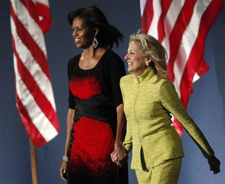 Michelle Obama and Jill Biden hold hands as they arrive onto the stage following Obama's speech during his election night rally after being declared the winner of the 2008 presidential election in Chicago November 4, 2008. REUTERS/Jim Young