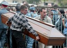<p>Люди несут гроб во Владикавказе 4 сентября 2004 года. В результате взрыва бомбы, приведенной в действие смертницей в центре североосетинской столицы, погибли 11 человек, сообщили правоохранительные органы и местные власти. REUTERS/Sergei Karpukhin</p>