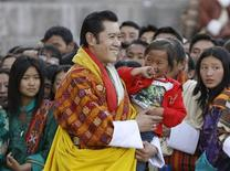 <p>Bhutan's King Jigme Khesar Namgyel Wangchuck carries a child in the courtyard of Tashichhodzong Palace during celebrations marking his coronation ceremony in Thimphu November 6, 2008. With medieval tradition and Buddhist spirituality, a 28-year-old with an Oxford education assumed the Raven Crown of Bhutan on Thursday, to guide the world's newest democracy as it emerges into the modern world. REUTERS/Desmond Boylan</p>