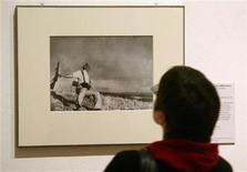 """<p>Foto de archivo de un visitante mirando la fotografía """"Muerte de Un miliciano"""" en la retrospectiva de Robert Capa en Berlín, 21 ene 2005. """"Muerte de un miliciano"""" es una de las fotografías de guerra más famosas de la historia, y también una de las más polémicas. REUTERS/Arnd Wiegmann AKW/JOH</p>"""