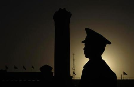 A paramilitary policeman stands guard in front of the Great Hall of the People, in Beijing March 15, 2008. REUTERS/Jason Lee