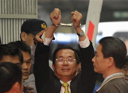 Former Taiwan President Chen Shui-bian shows his handcuffed hands to the media while being sent from the prosecutors' office to the Taipei District Court November 11, 2008. REUTERS/Stringer
