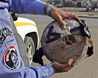 <p>An Iraqi policeman holds a wrapped defused land mine, meant to be used as an improvised bomb, found on a road in Baghdad's Sadr city, January 6, 2006. REUTERS/Kareem Raheem</p>
