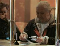<p>Женщина пересчитывает деньги в ломбарде в центре Москвы 14 ноября 2008 года. Когда весь мир страдает от мирового финансового кризиса, московские ломбарды процветают. REUTERS/Alexander Natruskin</p>