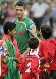 <p>Cristiano Ronaldo é cercado por crianças antes de treino de Portugal em Brasília na terça-feira. REUTERS/Bruno Domingos (BRAZIL)</p>