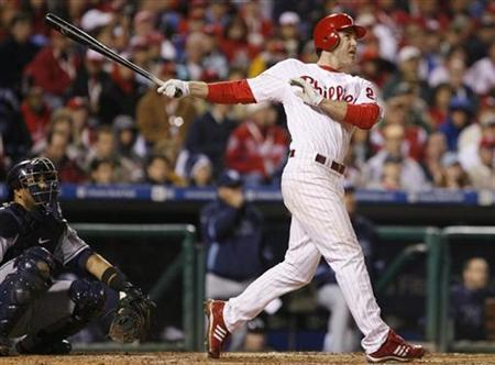Philadelphia Phillies' Chase Utley hits a solo home run in front of Tampa Bay Rays catcher Dioner Navarro during the sixth inning in Game 3 of the World Series in Philadelphia October 26, 2008. REUTERS/Tim Shaffer