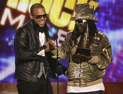 Singer Chris Brown (L) receives his award for pop/rock favorite male artist from T-Pain at the 2008 American Music Awards in Los Angeles November 23, 2008. REUTERS/Mario Anzuoni