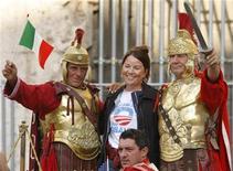 <p>Turista posa con due uomini vestiti da centurioni romani nei pressi del Colosseo, a Roma. REUTERS/Chris Helgren</p>