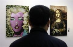 """<p>Посетитель на выставке современного искусства художницы и скульптора Цзюй Доци в Пекине 25 ноября 2008 года. Перечные глаза """"Моны Тофу"""" смотрят на вас из-под струящихся лапшичных прядей, а томатная кожа """"Капустной Монро"""" румянится на выставке современного искусства художницы и скульптора Цзюй Доци в Пекине. REUTERS/Jason Lee</p>"""