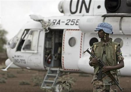 A Rwandan soldier serving with the United Nations-African Union Mission in Darfur (UNAMID) stands guard next to a UN helicopter in the village of Dar es Salam, North Darfur in this handout picture taken July 9 and released on July 14, 2008. REUTERS/Albany Associates/Stuart Price/Handout