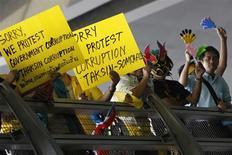 <p>Участники акции протеста держат лозунги, захватив международный аэропорт в Бангкоке, 26 ноября 2008 года. В результате серии взрывов небольшой мощности пострадали несколько участников антиправительственной акции протеста, заблокировавших аэропорт Бангкока в среду. REUTERS/Chaiwat Subprasom</p>