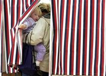 <p>Elyse Holmes, 2, peaks out as her mother Helen Holmes votes at Madbury Town Hall in Madbury, New Hampshire November 4, 2008. REUTERS/Adam Hunger</p>