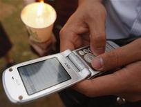 <p>Un giovane manda un sms dal suo telefono REUTERS/Lee Jae-Won</p>