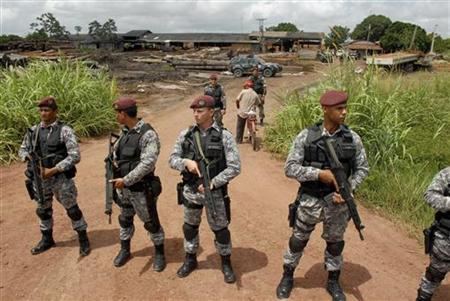 Brazilian federal policemen stand guard at the entrance to the Madeflora sawmill as government environmental inspectors search for logs that were cut illegally from virgin Amazon rain forest, as part of the Arch of Fire operation to stop illegal logging, near Tailandia, 180 km (112 miles) south of Belem, at the mouth of the Amazon River, February 27, 2008. REUTERS/Paulo Santos