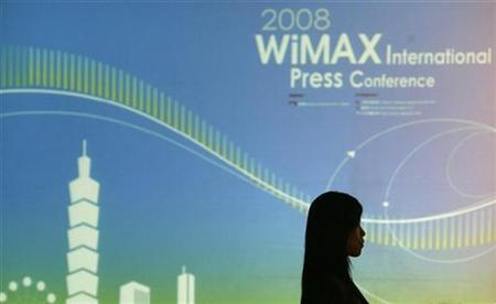 A woman walks past a WiMax sign during a news conference in Taipei April 21, 2008. REUTERS/Pichi Chuang