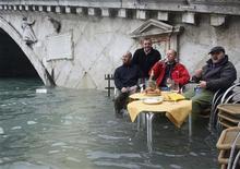 <p>Residentes desayunan en un área inundado en Venecia 1 dic 2008. En un día con mal tiempo en toda Italia, Venecia se preparaba el lunes para una previsión de crecida de las aguas que podría llegar al mediodía al nivel récord alcanzado por última vez hace 22 años: 160 centímetros. REUTERS/Manuel Silvestri</p>
