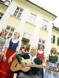 """<p>Foto de archivo de Maria von Trapp tocando la guitarra junto a unas niñas en frente de su antigua mansión en Salzburgo, Austria, 24 jul 2008. Autoridades de Salzburgo, la ciudad donde se encuentra la casa original del filme """"La Novicia Rebelde"""", han cancelado los planes de convertir a la mansión de la familia von Trapp en un hotel, según reveló la compañía detrás de la idea. REUTERS/Leonhard Foeger</p>"""