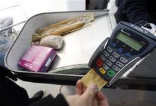 <p>Un uomo paga la spesa in un supermercato con una carta di credito. REUTERS/Eric Gaillard (FRANCE)</p>