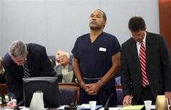 <p>O.J. Simpson listens with his attorneys Gabriel Grasso (L) and Yale Galanter as District Court Judge Jackie Glass (not in photo) reads his sentence at the Clark County Regional Justice Center in Las Vegas, Nevada December 5, 2008. REUTERS/Issac Brekken/POOL</p>