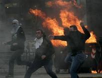 <p>Участники беспордков бросают камни в полицейских перед горящими баррикадами в Афинах, 7 декабря 2008 года. Беспорядки, ставшие самым серьезным массовым волнением за многие годы, вспыхнули в нескольких греческих городах, после того, как полиция застрелила мальчика-подростка в столице государства. REUTERS/John Kolesidis</p>