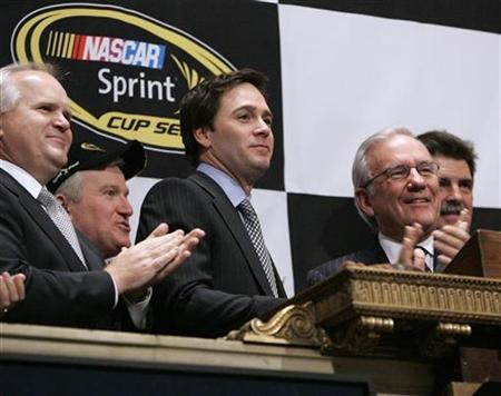 Jimmie Johnson (C), the second driver to win three consecutive NASCAR Sprint Cup championships, rings the opening bell of the New York Stock Exchange, December 3, 2008. Standing with Johnson, Sprint CFO Bob Brust (2nd R), Robert Niblock (L), Chairman and CEO, Lowe's Companies, Inc, and Mike Helton (R), President of NASCAR. REUTERS/Chip East